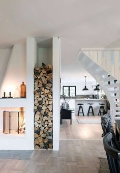 Cabin interior inspiration. white and wood. wood storage next to fireplace.