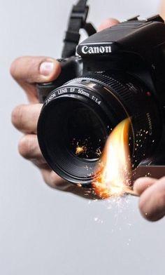 Uma pessoa segurando uma câmera na mão e na outra está com um fósforo aceso próxima a lente da câmera