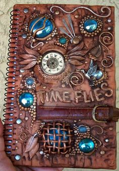 This is a blank book that I've decorated with polymer clay, aqua blue glass gems, sterling silver, brass and a watch and watchband.