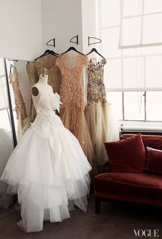 Sample dresses with tiers of tulle and intricate detailing hang by the window in the studio.