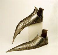 Sapatos de armadura em ferro, de bico revirado. Ano de 1490 - MMA