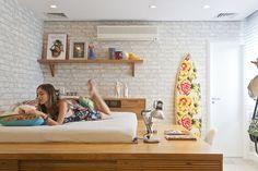 Cama alta, chaise com lona de caminhão, prancha florida e papel de parede com efeito de tijolos brancos no quarto da adolescente.