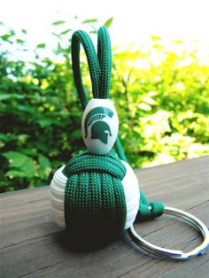 Michigan State Spartans Paracord Monkey Fist Keychain Handmade by katina Monkey Fist Keychain, Monkey Fist Knot, Paracord Knots, 550 Paracord, Michigan State Spartans, Msu Spartans, Self Defense Keychain, Baby Receiving Blankets, Paracord Projects