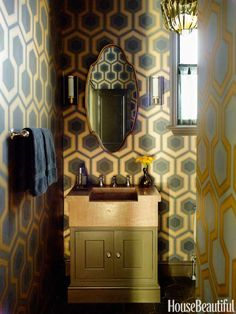 The mod honeycomb pattern of Hicks Grand wallpaper by Lee Jofa enlivens the powder room.