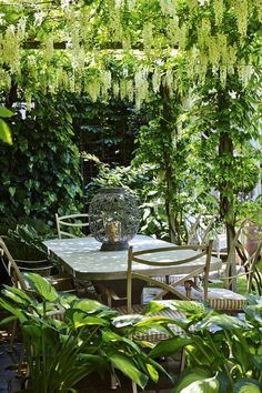"This wisteria-clad pergola in the garden of a London flat designed by [link url=""http://www.charlottecrosland.com/""]Charlotte Crosland[/link] provides shade for outdoor dining. Hanging wisteria and striped cushions make this an idyllic outside space."