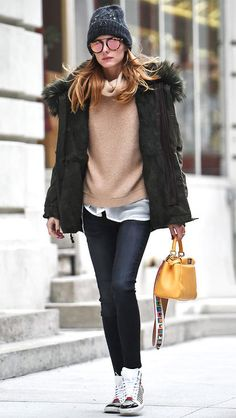 Celebrity winter outfit ideas: Olivia Palermo in a camel sweater, parka, beanie, sneakers and Westward Leaning sunglasses