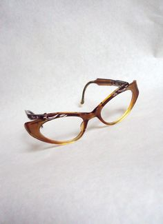 62bcd7b0cad53 1950s Cola lucite cat eye spectacles with plum engraved brow. via Etsy.  Face Jewellery
