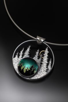 Joan M Tenenbaum | Northern Lights - Breathe The Night Enameled Pendant Materials: Sterling Silver, Cloisonné Enamel, 14 and 18 Karat Gold, Green Sapphire Sterling silver pendant with an enameled centerpiece showing northern lights in the sky behind spruce trees against a backdrop of tall spruce trees and a full moon. Photo credit: Doug Yaple