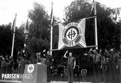 "Members of the Fascist 'French Popular Party' accompanied by their paramilitary wing known as the 'Malice' (""Militia"") give salute during a party rally held in celebration of the Party's 6th anniversary since its initial founding in 1936. Arènes de Lutèce, Paris, German-occupied France. July 1942. Despite France's occupation by the German Reich in 1940, the FPP was never actually put into power. Instead, both Vichy and German officials utilized them for anti-communist/anti-partisan…"