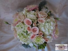 Vintage style bouquet with pinks, whites, and peaches. Mix of dahlias, roses, hydrangea, and other seasonal flowers.