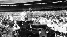 March 1954: Queen Elizabeth and Prince Philip drive in a gleaming Land Rover through excited schoolchildren at the MCG. Picture: News Limited.