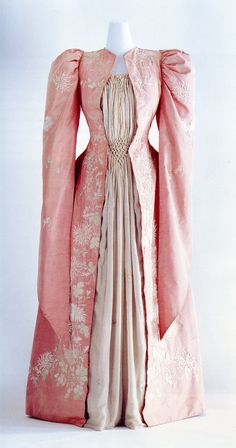 """This tea gown was made in Japan to an order for Western market. Its shape is a mixture of details of the 18th century style and the medieval style, which was revived at the end of the 19th century. It is made of taffeta, known as """"seigo"""" in Japan, and embroidered with chrysanthemum flowers in a Japanese embroidery technique known as """"nikuirinui"""". A tea gown is an elegant hostess' dress used as informal, indoor wear from the late 19th century to the beginning of 20th century."""