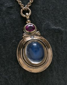 """James Meyer.  One-of-a-kind 18k yellow gold cast, forged, and fabricated pendant. The 5.50 ct. Ceylon blue moonstone cabochon, 9.5mm x 11.5mm is set in a 22k gold bezel. The 2.58 ct. faceted ruby is set in a green gold bezel while the 0.015 ct. old mine cut diamond is gypsy set. The piece is set on a 16"""" chain with clasp."""