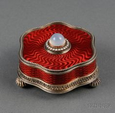 Faberge Scarlet Guilloche Enameled, Goldwashed Silver, and Stone-set Electric Bell, St. Petersburg, 1908-17, maker likely Karl Gustav Arunfelt, stylized floriform, beaded upper rim, leaftip lower rim, on three reeded ball feet, with overall scarlet basse taille enamel, central moonstone cabochon button in surround of crimped collet-set seed pearls.