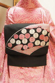 黒の地に、桃色美しく織り出された、鹿の子の雲と水玉のような菊花が彩る扇面が可愛い開き名古屋帯です。
