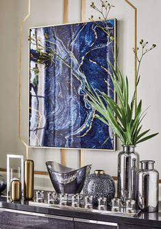 A striking feature upon any wall, the Set of 2 Marble Effect Panels feature abstract canvas prints in vibrant shades of blue, with hints of gold throughout.