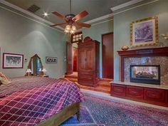 This rich bedroom features beautiful woodwork and a cozy fireplace. Love the colors, which are both elegant and relaxing. The dark plum really pulls everything together.