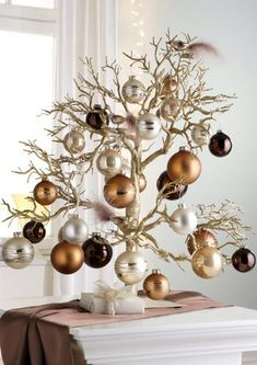 Tabletop Christmas Tree a great way to recycle that dead tree or shrub , a few snips & spray painting and you have a work of art for christmas , i would love this in a hallway entry....