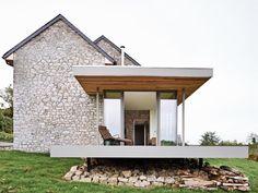 Casa in pietra, tetto a spiovente, veranda con vetrata
