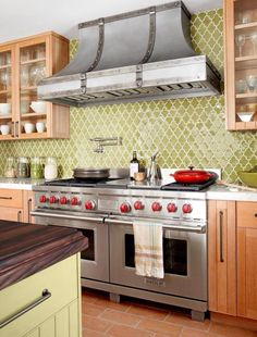 Stunning Kitchen with green morrocan tile backsplash and awesome vent hood. I'm in love.
