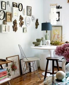 Eclectic framing mixed with sculptural wall art pieces. Like how some art is hung and others just placed on top of frames.
