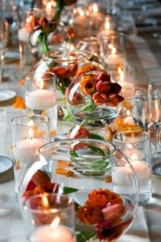 line a long table with flower-filled fish bowls and candles for simple yet dramatic centerpiece. Bonus: the centerpieces are low enough to still have a conversation!