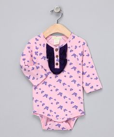 Little men get bow ties in front, so for little ladies, a layer of ruffles is quite fitting. They're framed by the perfect pattern while the row of wooden buttons on the front hints at this piece's eco-friendly roots.100% organic cottonMachine wash; tumble dryImported
