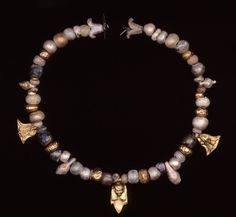 ancientpeoples:    Gold and Glass Necklace  Grave 1, Tharros  Phoenician  4th Century BC  Length: 31 cm  Necklace with three gold pendants including one of Hathor and 40 glass beads.   Source: British Museum