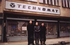 "Ralf Hütter poses by the ""Technomat"" sign, accompanied by Radio 1 DJ Josef Sedloň (on left) and Mladý Svět's (""Young World""-Eng.) writer Pavel Kracik (right) in the first picture. ""On the Peter's square in town Ralf is fascinated by the ""Technomat"" sign. ""What is it? A software shop?"" he asks and allows to be photographed under the inscription, which must mean something, because he dislikes being photographed."" 30th November 1991, Prague/"