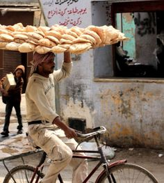 Bread vendor carrying bread tray with one hand on bicycle in Pakistan.