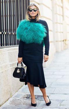 Janka Polliani wears a black sweater, skirt, green fur, top=handle bag, and black pumps