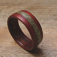 This stunning Red wood ring is made from the beautiful Padauk wood. The wood is a rich, bright red which perfectly contrasts the brass inlay. The brass inlay is made from real brass powder giving is a magical glow.  The strip of wood is chosen carefully for strength and appearance before the creation even begins. Each piece of wood is unique with its own grain and story. Much like each of us. Then it is soaked for at least 24 hours before it can be used. After this the wrapping and shaping…