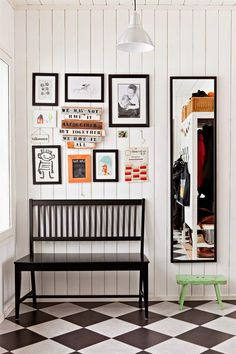 chic and functional entryway. black bench, gallery wall on white painted paneling