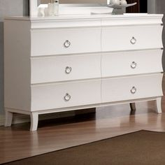 Six-drawer dresser with ring pulls and flared legs.   Product: DresserColor: WhiteFeatures: