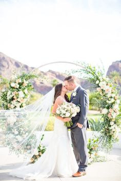 Symmetrically wrap a circular wedding arch in romantic peach and cream roses to create a semi-circle worthy of smooches! See more of this Blush + Mint Arizona Wedding with Circular Floral Arch at Mountain Shadows 30+ Creative Wedding Arches You Must See Right Now!  #weddingarch #outdoorweddingarch #weddingarchideas #wedding #confettidaydreams #weddingceremony #weddings #weddingideas #weddingplanning #weddingcanopy #weddingbackdrop