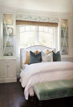 Another good example of how to perch a bed in a window, with attractive cabinets on either side. Layered window treatment.