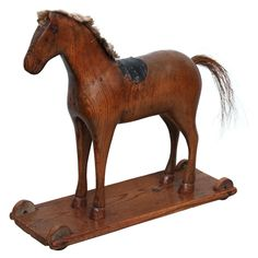 19th Century Swedish Horse Pull Toy Sweden Circa 1880 Sculptural Swedish 19th Century carved pine child's pull toy in the form of a horse, retaining its mane and leather saddles on original platform base retaining its wheels, the whole with lovely color and graphic form.