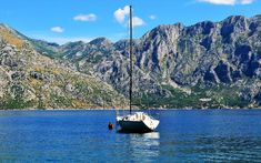 Photo about Photo of Kotor bay with cristal water a boat and a blue sky behind the mountains - Kotor Bay - Montenegro - July 2010. Image of mountains, kotor, july - 113952019