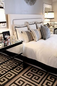 This black, grey & white bedroom has a reoccurring Greek key element; on the rug as well as the mirrors above the nightstands, which are also mirrored. I love the head board. Tres chic....V