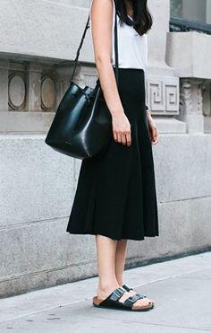 ホワイトトップス×ブラックフレアスカート。フェミニンなシルエットには抜け感のあるレザー小物を合わせて。