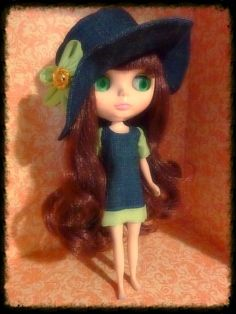 The set includes:  Denim hat with green flower decoration Denim dress with green decoration    doll is not included