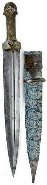 Kindjal / qama, 18th to 19th c, found throughout the Caucasus Mountain Region, from South Russia to Georgia (also known as 'Kama' locally), Armenia, Azerbaijan to North Iran,  double edged blade with central grooves on both sides. One side engraved presumably in Arabic script, horn hilt with two decorative medallion iron studs, blue-white textile decorated scabbard with 'Mirabotta' designs, iron loop with carrying ring, traces of gold damascening, leafy tendril and geometric décor, L: 51 cm.