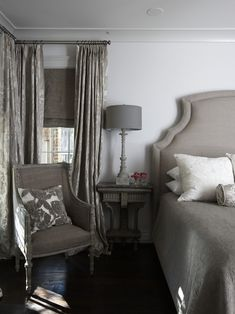 bedrooms - gray linen headboard gray French chair white gray embroidered pillow gray wood lamp gray damask drapes layered gray silk roman shades