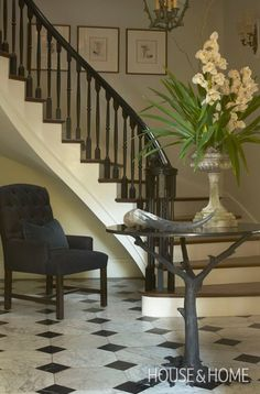 Photo Gallery: Classic French Style | House & Home A small space reborn into grand front foyer. The graceful, curving staircase with a dark glossy handrail and spindles/marble tiled floor make a great impression for this renovated Georgian-style home. Adding a chair and a nature-inspired statement table makes it an entry room, not just a transition space. Displaying art and decorating favourites — like horn and pedestal urn filled with orchids — completes the traditional, polished look.