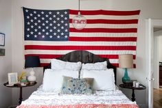 """""""In the master bedroom, an American flag makes for an eye-catching art piece behind the weathered-wood headboard, which was created for Lindsey by a DIY-savvy friend."""""""