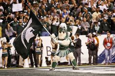 Sparty waves an MSU flag after Jeremy Langford ran in for a touchdown in the fourth quarter of the Big Ten championship game Saturday at Lucas Oil Stadium in Indianapolis. Michigan State won the game 34-24 and will now play in the Rose Bowl on Jan. 1, 2014. (Mike Mulholland | MLive.com)