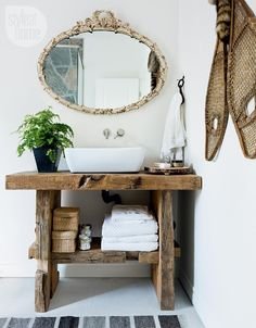 Bathroom design—The bathroom features a modern vessel sink and wall-mounted faucet atop a rough-hewn vanity made from old barn beams.