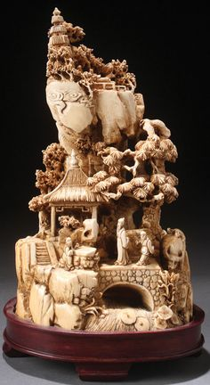 CHINESE CARVED IVORY MOUNTAIN SCENE, 19TH CENTURY. Fully carved in the round and pierced with pagodas, pine trees, and figures, one atop a water buffalo on a terraced rockery ground with stream at base below a bridge crossed by two figures.