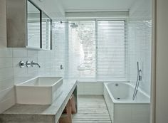 The master bath is a clean and spare space, a mixture of white and concrete. Courtesy of Copyright:Tobias Hochstein.