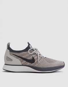 Modern racer from Nike in Pale Grey. Flyknit upper. Bootie-style construction. Lace-up front with round woven laces and Flywire cables. Heel pull tab. Molded heel counter. Zoom Air cushioning. Tonal stitching. Nike branding throughout. • Textile upper